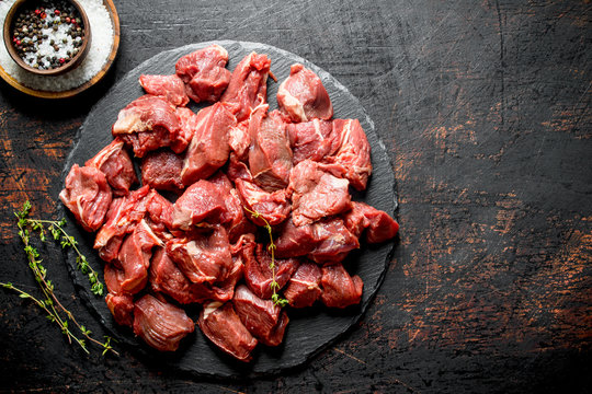 Cut raw beef on a stone Board with thyme and seasonings in bowls.
