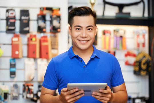 Salesman with tablet pc in the shop