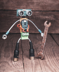 Robot made of parts of circuit boards with wrench, on wood background