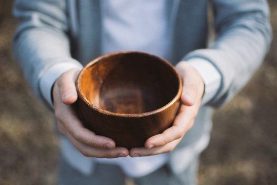 Men hand holding empty wooden bowl.