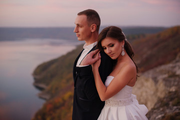 Beautiful wedding couple in love standing on the top pf the hill with wonderful view of the lake. Sunset. Groom and bride hugging