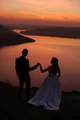 Silhouette of young wedding couple of groom and bride standing on the hill near the beautiful lake. Scenic landscape view with sunset. Bakota, Ukraine