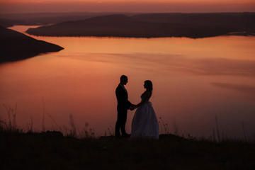 Wedding couple of groom and bride standing on the hill near the beautiful lake. Scenic landscape view with sunset. Silhouette