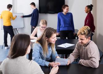 active classmates having animated talks at break between classes