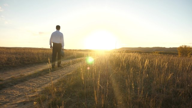 businessman in sunglasses goes down the country road with a briefcase in his hand. The entrepreneur works in a rural area. a farmer inspects land at sunset. agricultural business concept.