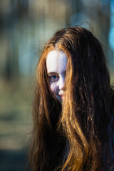 Close-up portrait of cute young girl with long bright red hair outdoors.