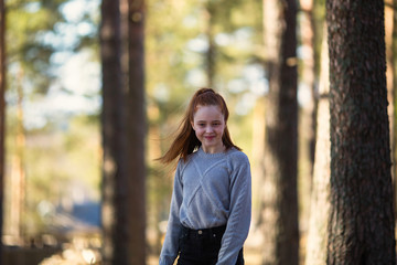 Twelve-year-old girl with long red hair posing in a summer pine Park.
