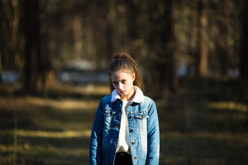 Twelve-year-old girl in a denim jacket posing in a summer pine Park.