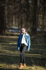 Cute eleven-year-old girl posing in a denim jacket.
