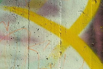 Concrete wall with yellow Spray stripes and purple color. Abstract background.