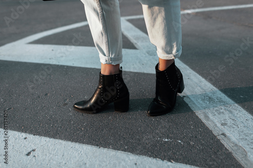 2b94589d7f05f Women s legs in leather fashionable black heeled shoes in stylish jeans on  a city street.