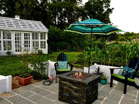 Beautiful Garden Scene with Patio, raised beds, andirondack chairs and umbrella around a gas firepit, with a lovely white greenhouse in background