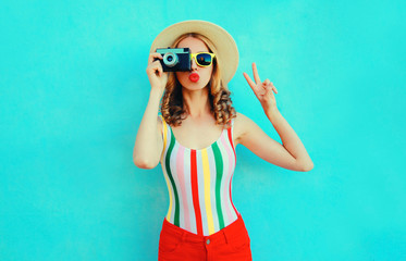 Colorful young woman holding retro camera, blowing red lips sends air kiss in summer straw hat having fun on blue wall background