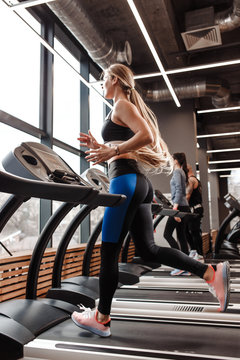The athletic girl with long blond hair dressed in a sportswear is running on the treadmill in front of the windows in the modern gym
