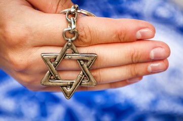 A hand of a young woman holding a key chain with a Star of David, traditional Jewish symbol. A concept image for the international Holocaust remembrance Day, Holocaust memorial.