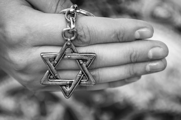 A hand of a young woman holding a key chain with a Star of David, traditional Jewish symbol. A concept image for the international Holocaust remembrance Day, Holocaust memorial. Black and white image