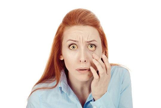 Woman checking her health condition looking into her eye