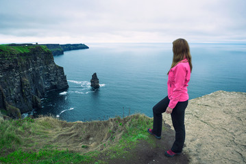 Wall Mural - Young girl standing at the cliffs of Moher