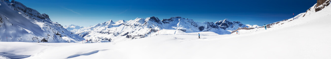 Fototapete - Beautiful winter landscape with Swiss Alps. Skiers skiing in famous Engelgerg - Titlis ski resort, Switzerland, Europe