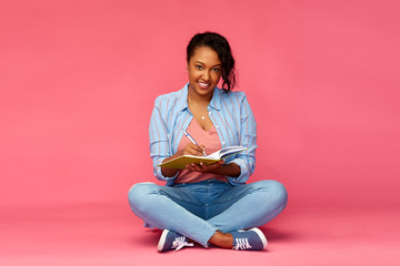 education, high school and people concept - happy african american young student woman writing to diary or notebook sitting on floor over pink background