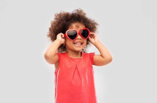 childhood, valentine's day and summer concept - happy little african american girl in heart shaped sunglasses over grey background