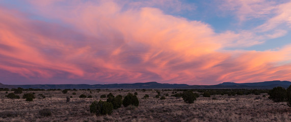 Sunset illuminates swirling dramatic clouds over the desert along Route 66 in Arizona
