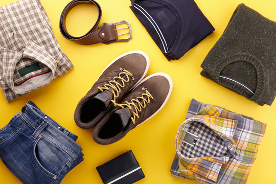 Mens casual clothing outfits and accessories flat lay on yellow background, top view