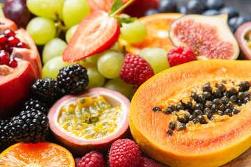 Wall Mural - Delicious healthy fruit background mango papaya strawberries oranges passion fruits berries, selective focus