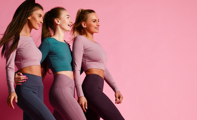 Group of three sport girls international friends posing on pink background. Sporty young women in green and purple Wall mural