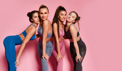 Group of four sport girls international friends posing on pink background. Sporty young woman in...