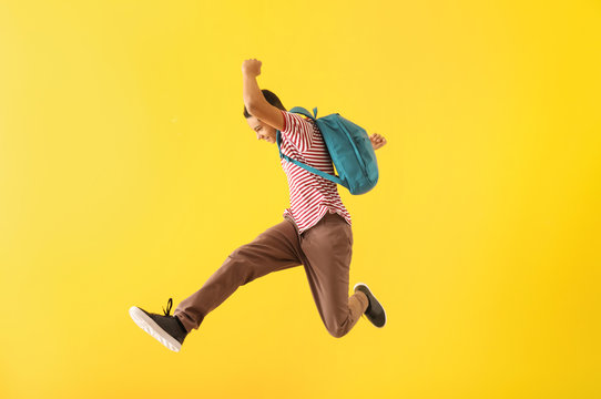 Portrait of jumping African-American teenage boy on color background