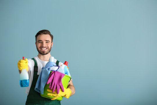 Portrait of male janitor with cleaning supplies on grey background