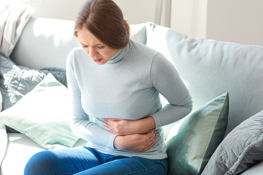 Young woman suffering from stomachache at home