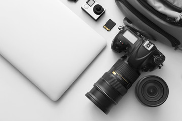 Modern equipment of professional photographer with laptop on light background Fototapete