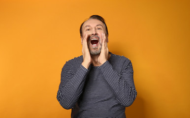 Portrait of screaming mature man on color background