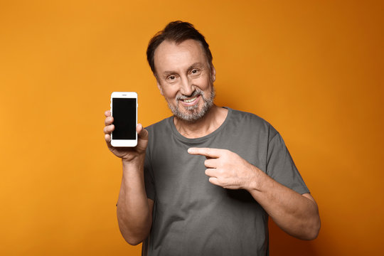 Portrait of handsome mature man with mobile phone on color background