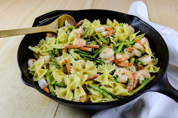 Freshly made bowtie pasta with asparagus and shrimp in a cast iron pan