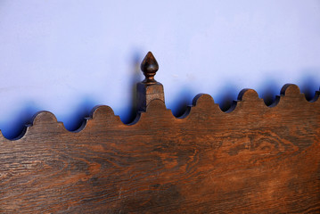 wavy top of wooden bench in front of blue wall