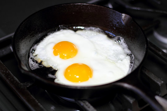 Two eggs frying sunny-side up in a cast iron pan on the stove.