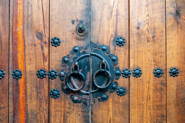 Korean wooden door panels decorated with old black metallic ring handles at a house in ancient village in Jeonju, South Korea