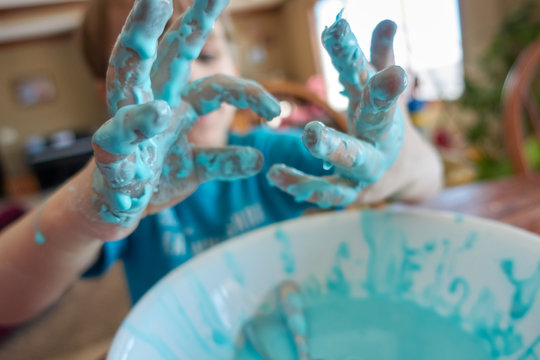 young child with focus on slime covered hands