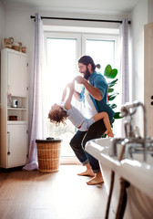 Small girl with young father in bathroom at home, having fun.