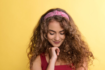 Portrait of a young woman with headband in a studio on a yellow background.