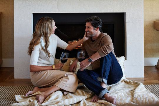 Mature couple connecting in front of fireplace in hotel room
