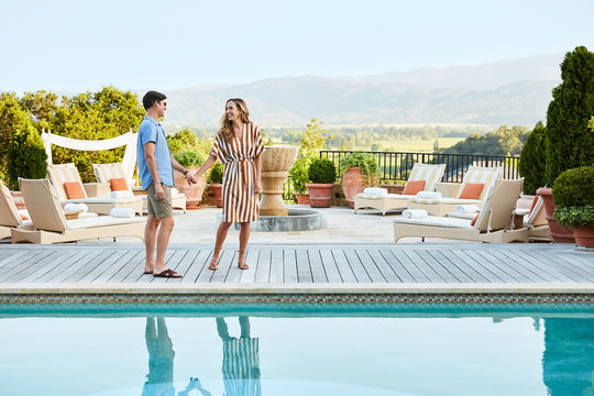 Couple standing by pool at luxury resort talking and looking at each other