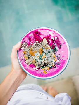 Tropical smoothie bowl in hand