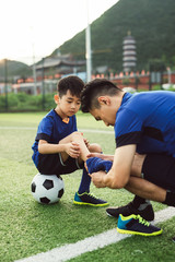 Father helping son dressing up in soccer uniform