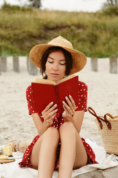 Woman on beach reading book