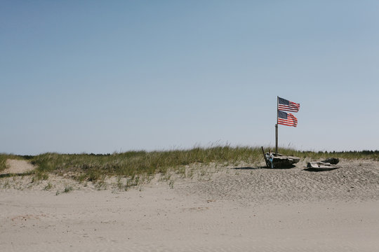 double American flags wave in wind above beach