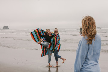mother takes cellphone picture of daughters at ocean